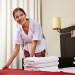 Zimmermädchen macht Bett im Hotel